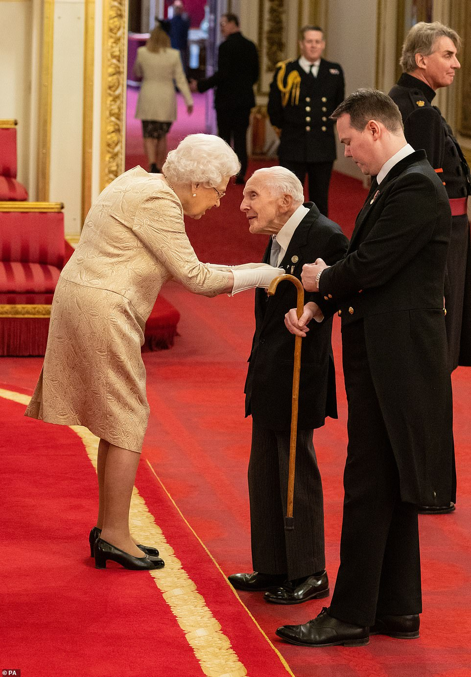 Queen dons gloves at an investiture for first time since 1954 amid coronavirus fear