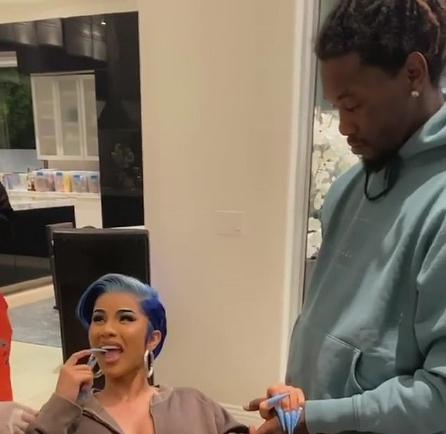 Cardi B holds Offset's hand as she gets sternum piercings